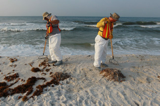 Workers on June 7, 2010, clean up oil residue from Pensacola Beach in Florida.