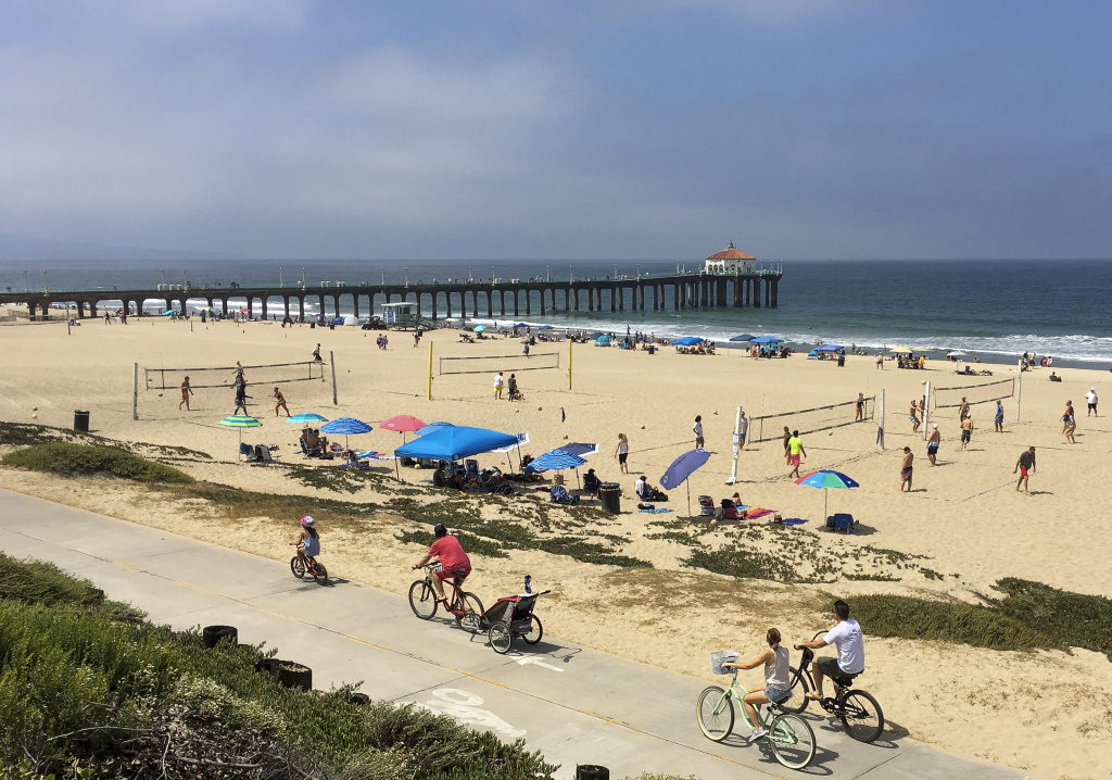 File: People enjoy the cooler weather in Manhattan Beach, Calif., Sunday, June 18, 2016. Skies cleared intermittently and then a steady onshore breeze kept the marine layer pressed against the shoreline.