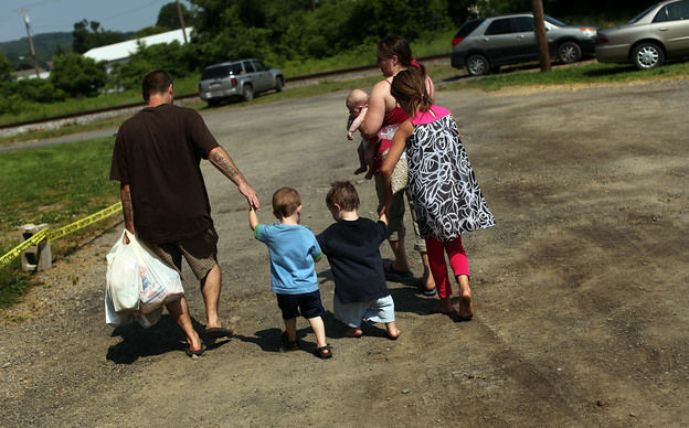 Members of the Dolan family walk home with bags of food from the Food Bank of the Southern Tier Mobile Food Pantry in Oswego, N.Y., in June. Food banks across the nation are reporting giant spikes in demand.