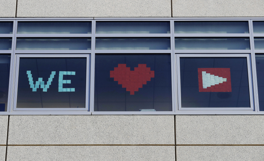 A sign for YouTube is displayed from windows at a Walmart corporate office in San Bruno, Calif., Tuesday, April 3, 2018. A woman opened fire Tuesday at YouTube headquarters, wounding some people before fatally shooting herself as terrified employees huddled inside, police and witnesses said.