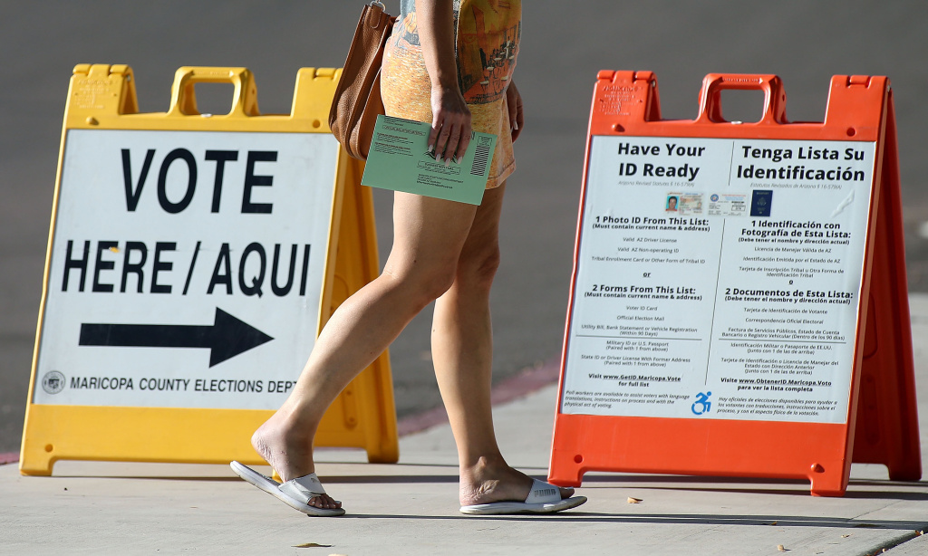 An Arizona voter carries her ballot to a polling place to vote in the state's Primary on August 28, 2018 in Phoenix, Arizona.