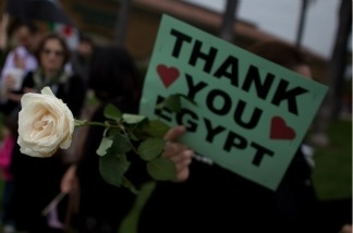 A Syrian woman holds a rose and a sign thanking the people of Egypt for continuing the wave of protests across the Middle East at a demonstration in Irvine, Calif., on May 7.
