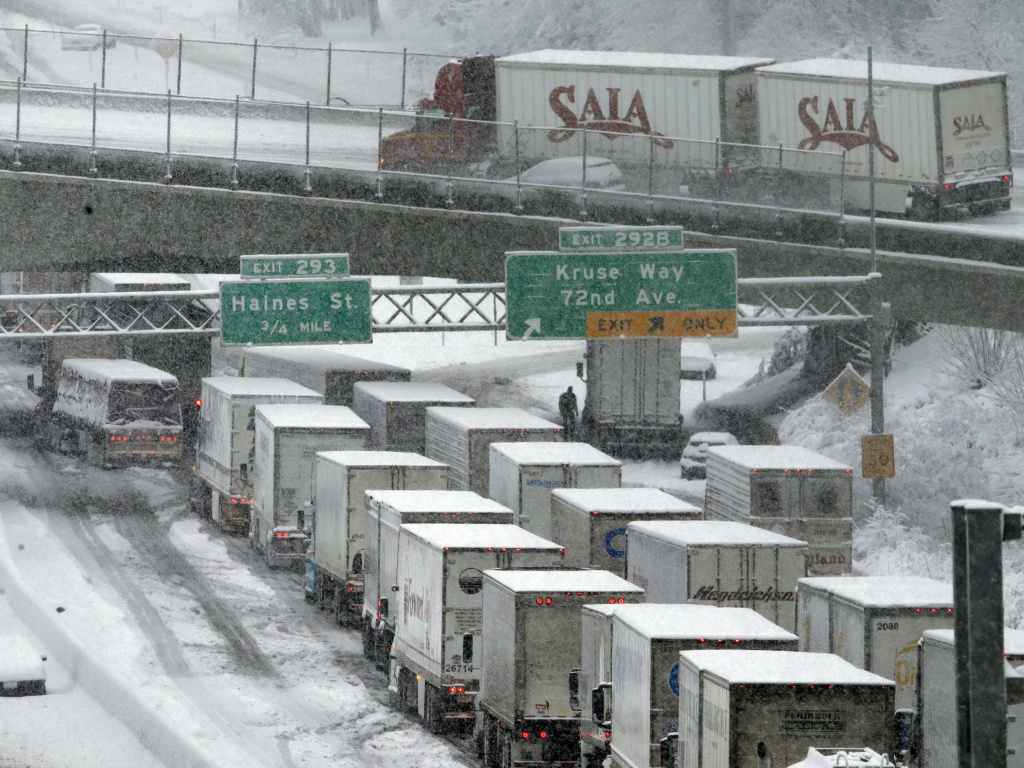 Early morning traffic backs up on Interstate 5 during a Jan. 11 snowstorm in Portland, Ore. Truck drivers say such conditions, combined with limitations on their working hours, cost them a lot of money because of their mileage-based pay.