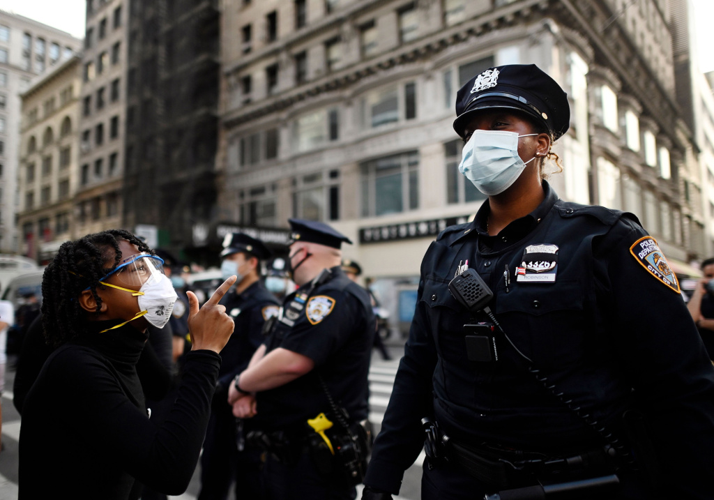 Protestors shout in front of NYPD officers during a