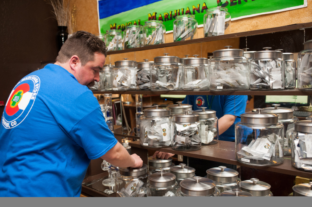 Sam Walsh, a budtender, sets up marijuana products as the 3-D Denver Discrete Dispensary prepares to open for retail sales on January 1, 2014 in Denver, Colorado. Legalization of recreational marijuana sales in the state went into effect at 8am this morning.