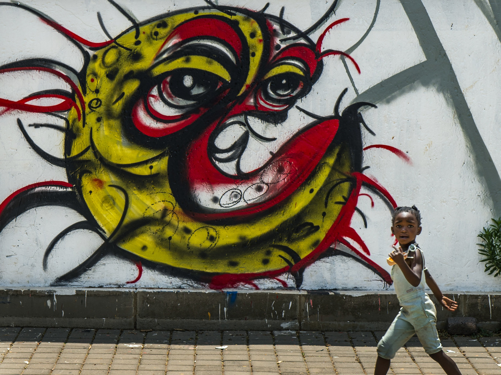 A child walks past a COVID-19 graffiti in Soweto's Orlando West township near Johannesburg, South Africa, on Thursday. Africa has surpassed 2 million confirmed coronavirus cases as the continent's top public health official warns that