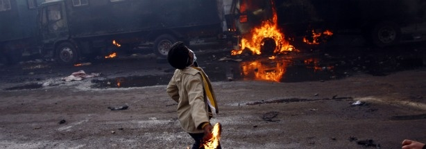 An Egyptian demonstrator throws a fuel bomb at anti-riot police vehicles in the northern city of Suez on January 28, 2011 as protests demanding the ouster of President Hosni Mubarak continue around the country.