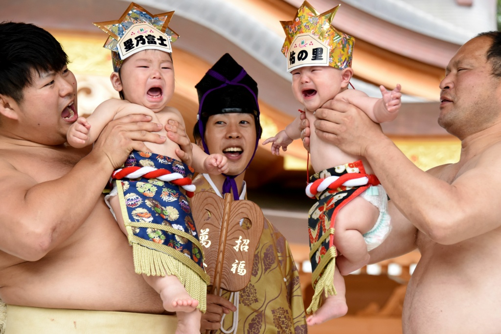 Sumo wresters hold up crying babies in front of a referee clad in a traditional costume during a