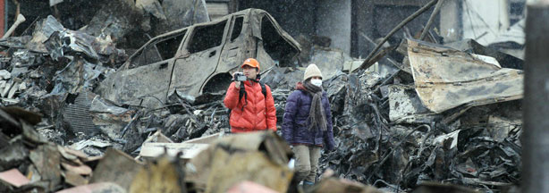 A couple walks under falling snow amongst the rubble in Yamada, Iwate prefecture, on March 15, 2011.