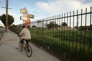 A man bicycles past a lot, vacated years ago when a long-established business failed in Compton, California.