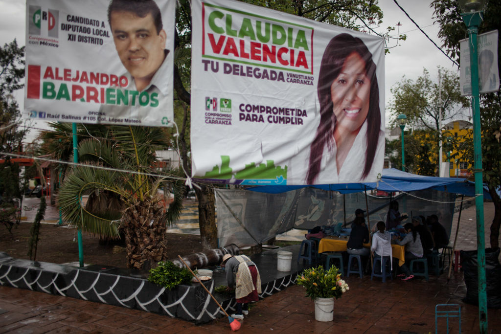 A family celebrates Father's Day near a park in the Peñón de Los Baños neighborhood of Mexico City in the shadow of campaign signs for candidates from Mexico's PRI party.