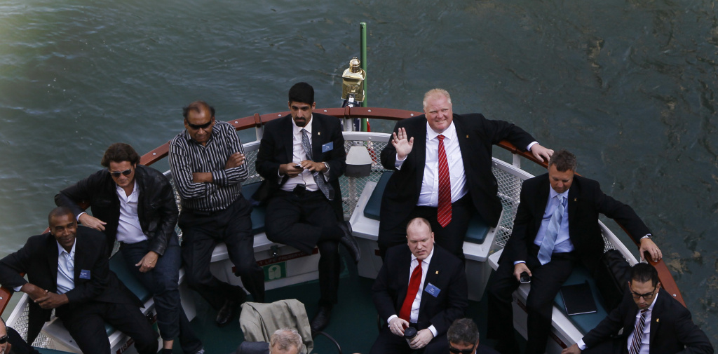 In this file photo, Toronto Mayor Rob Ford, top right, waves to photographers during a boat tour with members of the Toronto-Chicago Business Mission on the Chicago River waterfront Wednesday, Sept. 19, 2012, in Chicago. The Toronto City Council has voted to strip Ford of some of his powers and was poised Monday to strip most of those that remained.