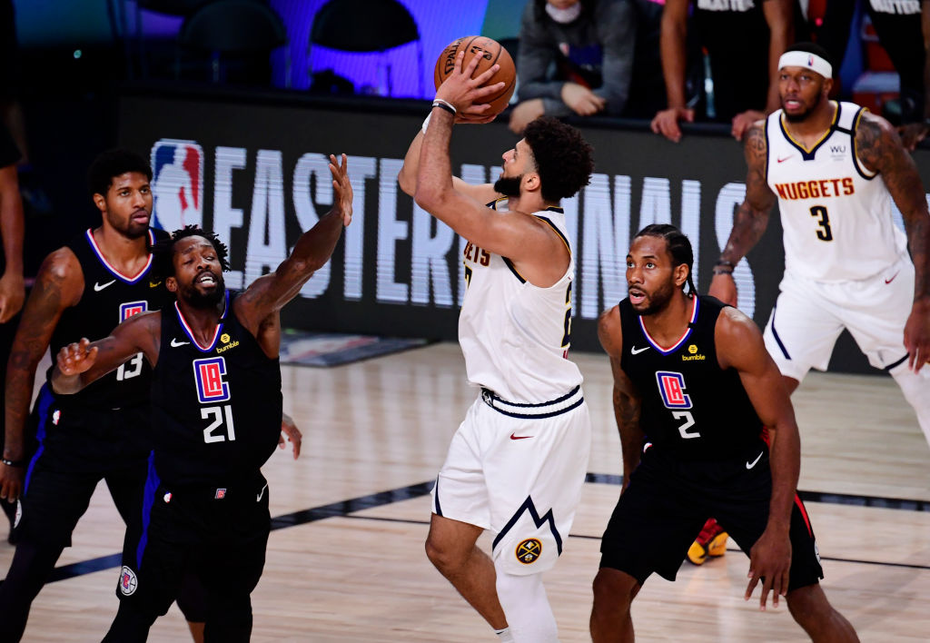 Jamal Murray #27 of the Denver Nuggets shoots the ball against Patrick Beverley #21 of the LA Clippers and Kawhi Leonard #2 of the LA Clippers during the fourth quarter in Game Seven of the Western Conference Second Round during the 2020 NBA Playoffs.