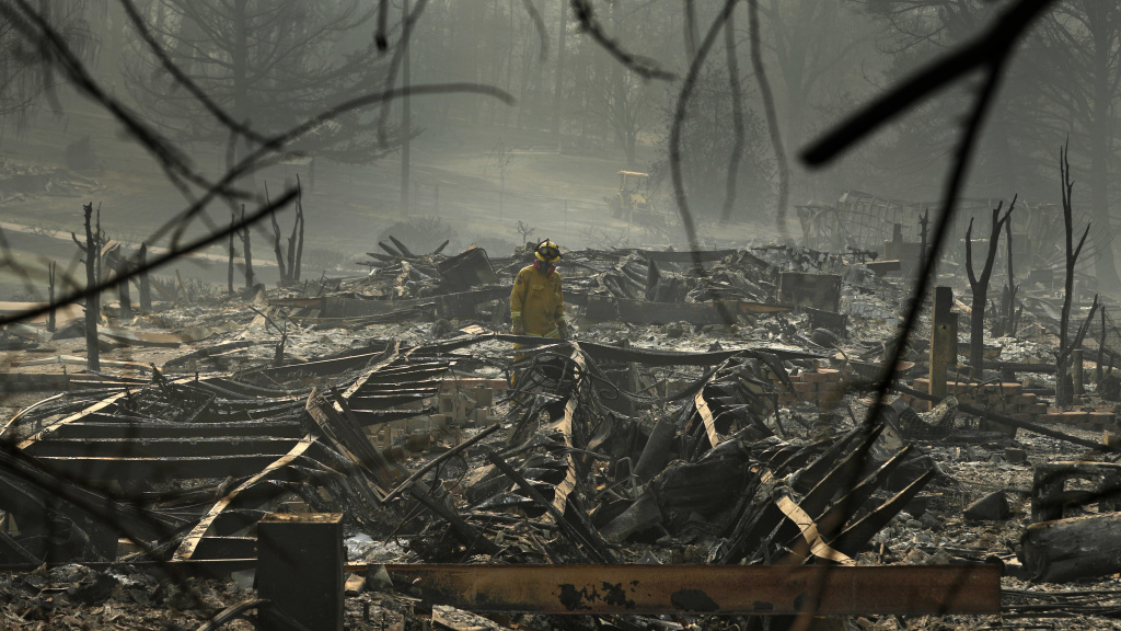 A firefighter searches a trailer park destroyed in the Camp Fire on Friday Paradise, Calif.