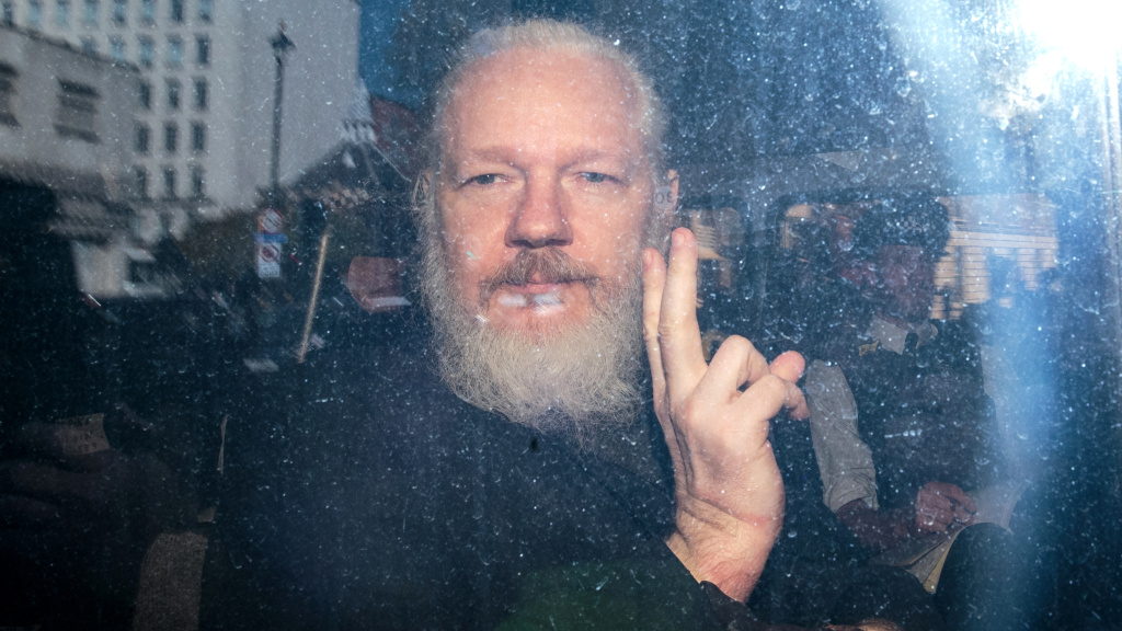 Julian Assange gestures seen inside a police vehicle on his arrival at Westminster Magistrates court in London on April 11. The WikiLeaks founder was sentenced to 50 weeks in prison by a British judge on Wednesday.