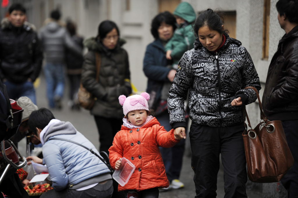A mother and child walk in Shanghai