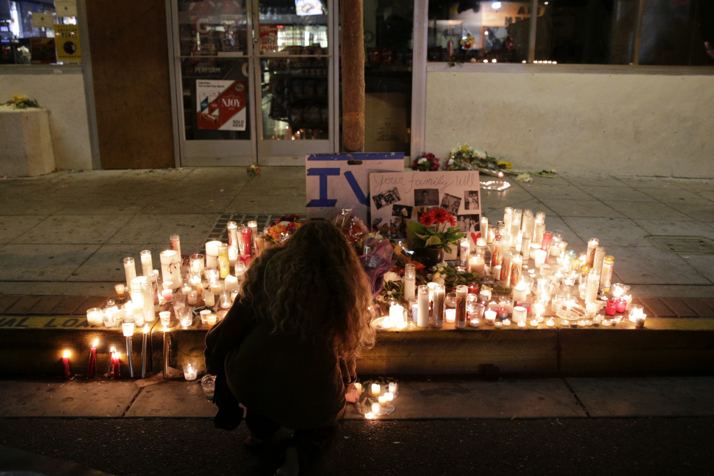 A woman places a candle in front of IV Deli Mart, where part of a mass shooting near UCSB took place, on Saturday, May 24, 2014, in the beach community of Isla Vista.