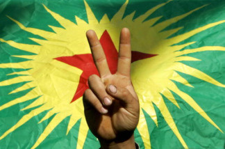 A demonstrator flashes a V-sign before outlawed PKK (Kurdistan Worker`s Party) flag on November 13 2005, during the 'democracy and peace' demonstration organized by local non-governmental groups and pro-Kurdish parties in Diyarbakir, predominantly Kurdish city of southeastern Turkey.