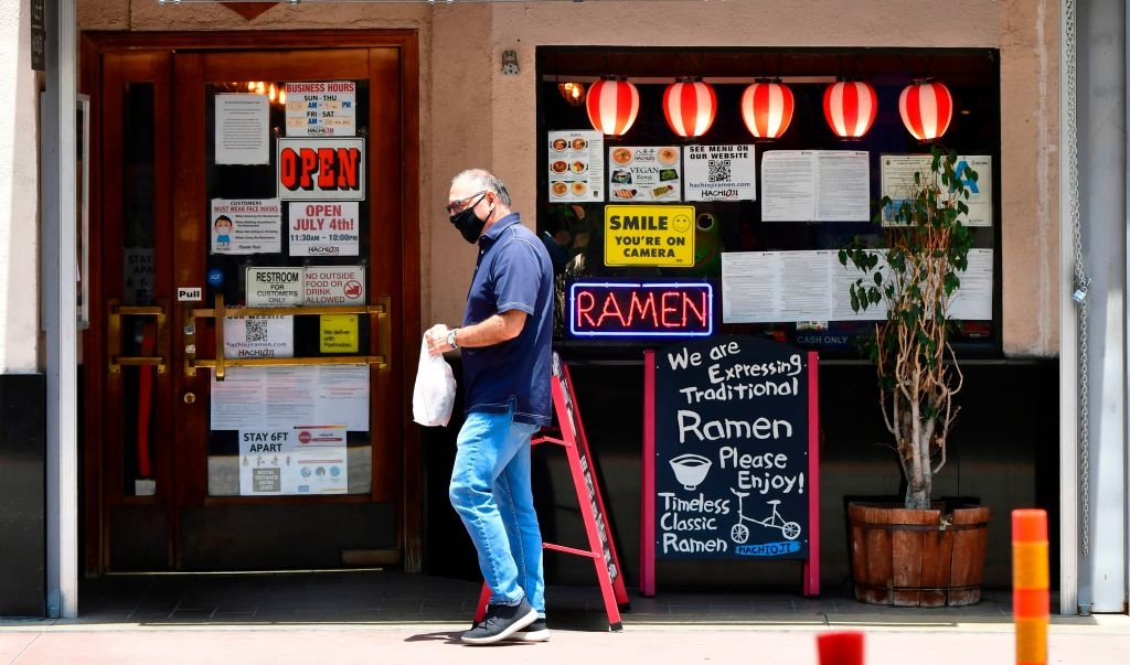 A man wearing a facemask walks past a Ramen restaurant in Los Angeles, California on July 1, 2020, after indoor restaurants, bars and movie theaters across much of California were ordered to close for at least three weeks.
