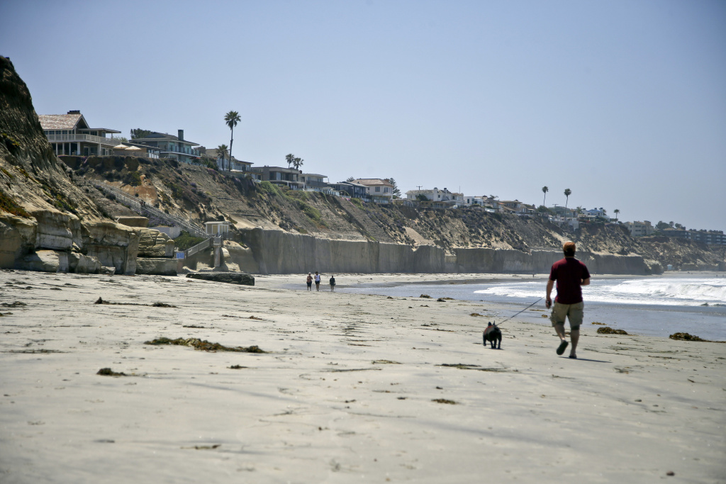 FILE PHOTO: Beachgoers walk the sand in Solana Beach, California, on May 20, 2013 below homes precariously perched atop cliffs. Some are supported by seawalls meant to hold back the ocean. A lawsuit before the California Supreme Court pits Encinitas homeowners against the state Coastal Commission over a seawall.