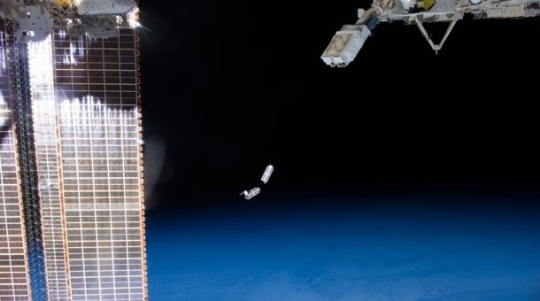 A set of NanoRacks CubeSats is photographed by an Expedition 38 crew member after deployment by the NanoRacks Launcher attached to the end of the Japanese robotic arm. The CubeSats program contains a variety of experiments such as Earth observations and advanced electronics testing. International Space Station solar array panels are at left. Earth's horizon and the blackness of space provide the backdrop for the scene.