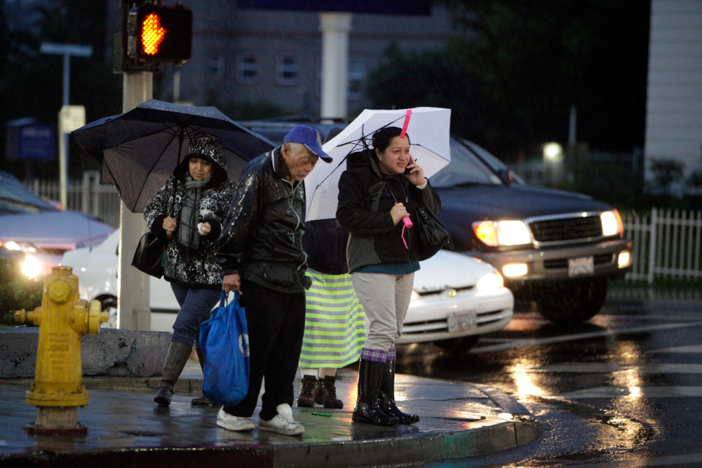 Morning commuters make their way a cross a city street in the heavy rain near downtown Los Angeles on Friday, Dec. 12, 2014. Street and freeway flooding snarled morning rush hour traffic and numerous accidents were reported. (AP Photo/Richard Vogel)