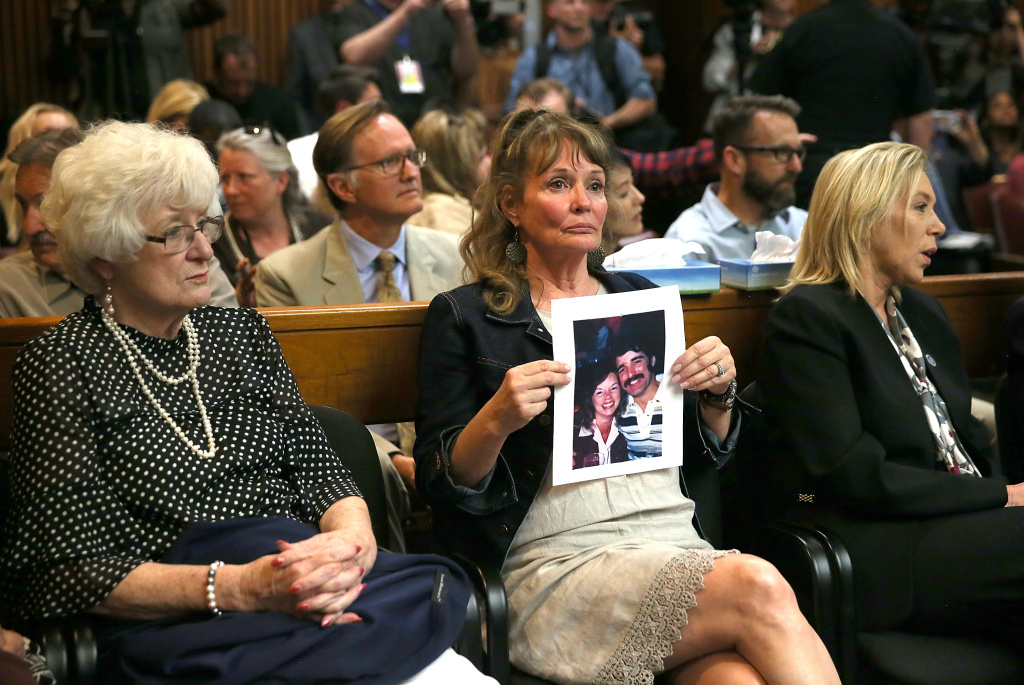 SACRAMENTO, CA - APRIL 27:  An attendee holds a photo of Cheri Domingo and her boyfriend Gregory Sanchez, who were killed in 1981, as she sits in the courtroom during the arraignment of Joseph James DeAngelo, the suspected