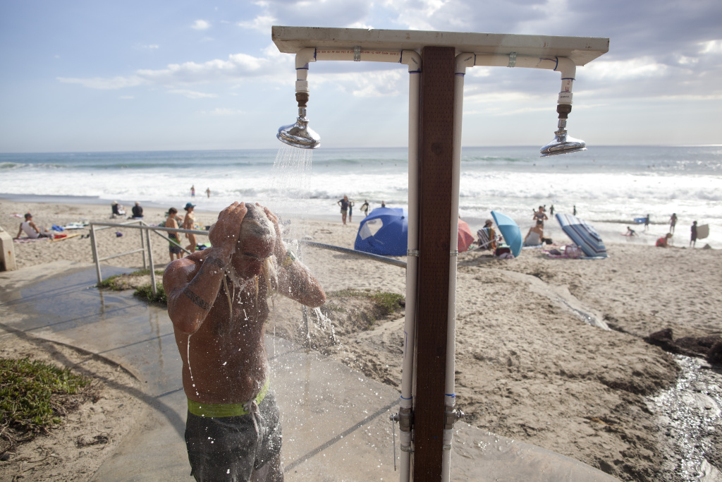 In file photo, Matt Doll of Santa Cruz cools off under a shower at San Clemente beach.