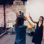 Critical Mass performance group's costume designer Lena Sands (R) tries out a new idea.