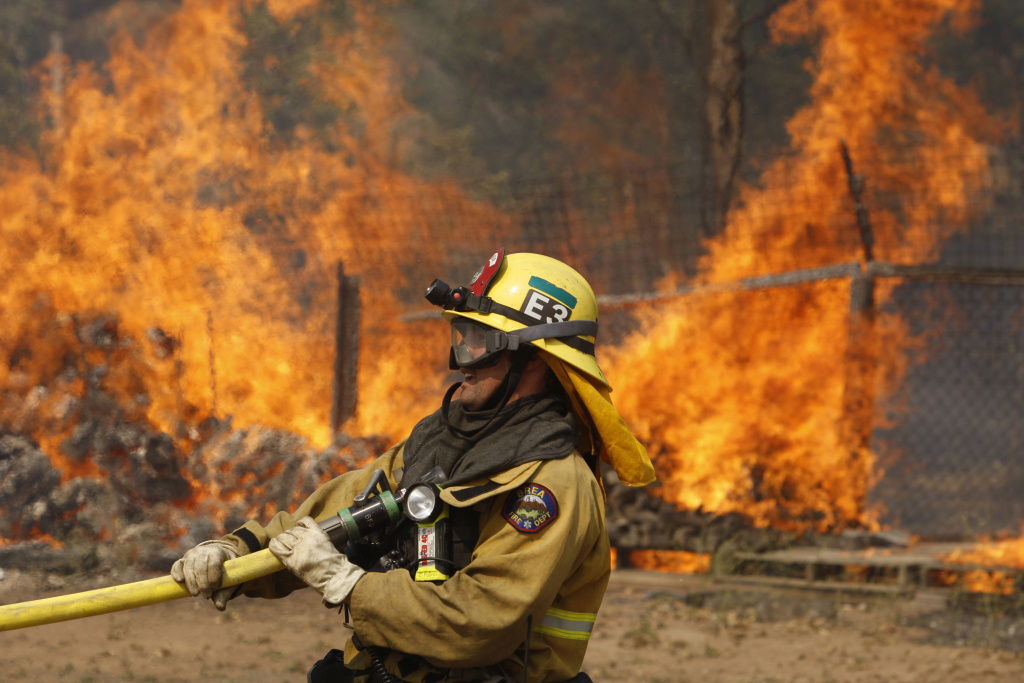 In this file photo from May, a firefighter pulls a hose in position while battling the Cocos fire in San Marcos, California. Officials said a juvenile is suspected of starting the fire, which destroyed 36 homes and one business.