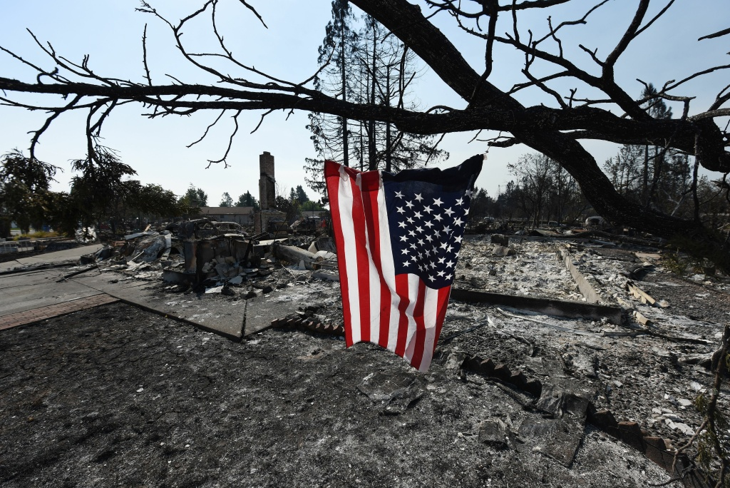 A US flag hangs on a tree in the widfire-ravaged Coffey Park neighborhood of Santa Rosa, California, on October 11, 2017.
