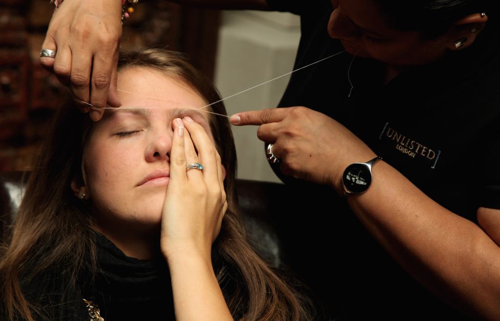 A woman has her eyebrows threaded at the Designer Couture Trunk Show hosted by Noelle Reno at The Collection on June 10, 2009 in London, England.