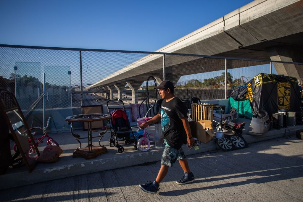 An unemployed upholsterer, Israel Yaxon 28 years-old, who has lived for one year on the street, walks outside his tent over the bridge of the 110 Freeway, during the novel Coronavirus, COVID-19, pandemic in Los Angeles California on May 25, 2020.