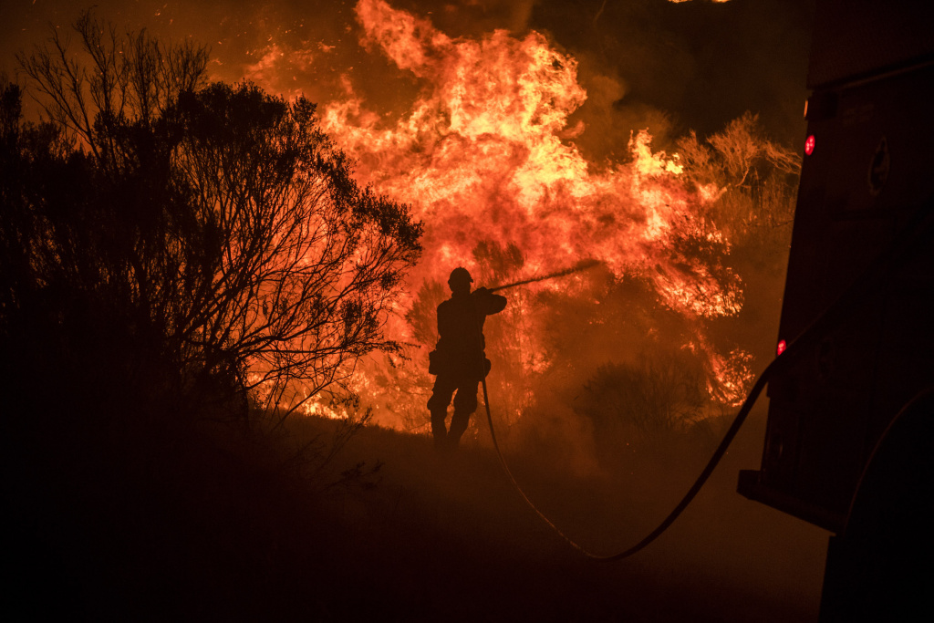 Vandenberg Air Force base firefighters help cool down a flare up during a firing operation Thursday night at the Sherpa Fire.