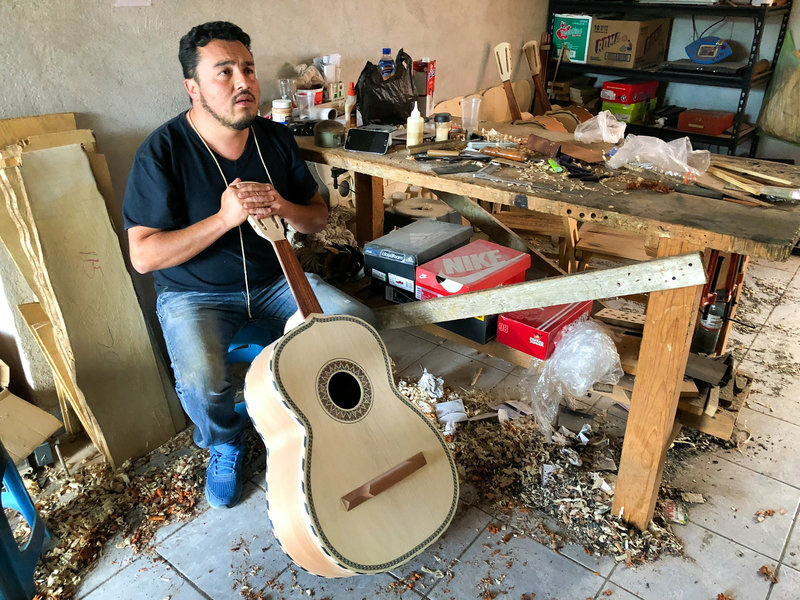 César Ivan Lemus, a third-generation Paracho artisan, shaves the neck of a guitarrón he's making. Lemus sells all types of instruments to mariachi schools and stores in the U.S. He says he's working as fast as he can to keep up with orders these days.