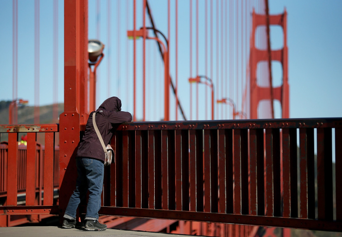 A visitor looks over the railing on the Golden Gate Bridge on March 12, 2014 in San Francisco, California. A long debated suicide barrier on the Golden Gate Bridge is a big step closer to reality after bridge officials approved a $76 million funding package for a net system that would prevent people from jumping to their deaths.
