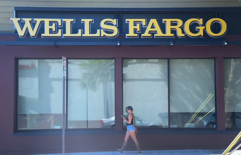 File: A woman walks past a Wells Fargo branch in Pasadena, California on September 28, 2016.