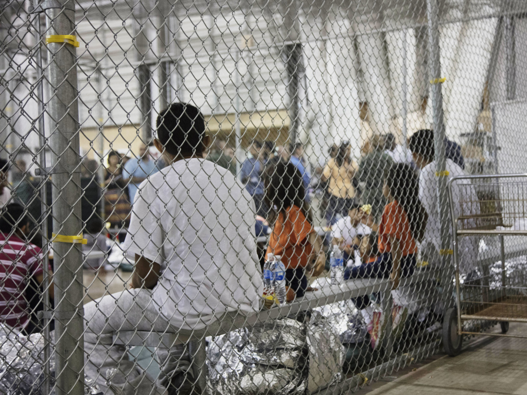 Migrants who've been taken into custody related to cases of illegal entry into the United States, sit in one of the cages at a facility in McAllen, Texas in June 2018. On Tuesday a federal judge ruled that asylum-seeking migrants can not be denied bond and held indefinitely.