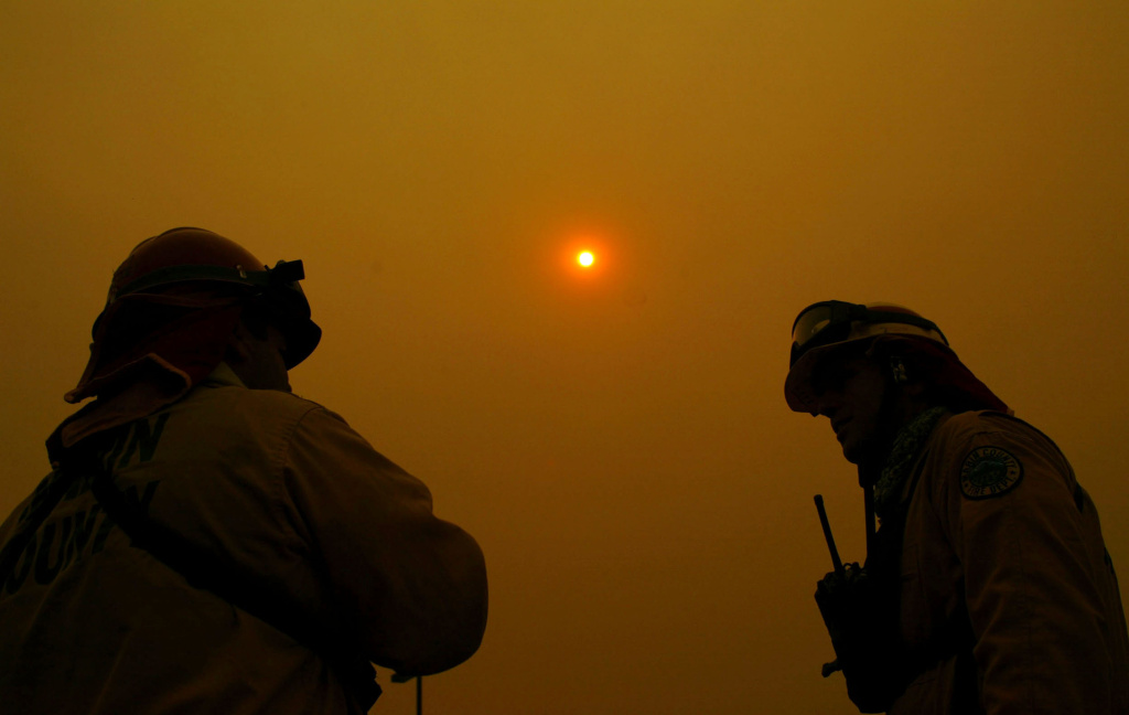 A pair of firefighters from Marin County Fire Department talk to each other as the sun is obscured by the ash clouds at the Cedar Fire October 27, 2003 near Lakeside in San Diego, California.