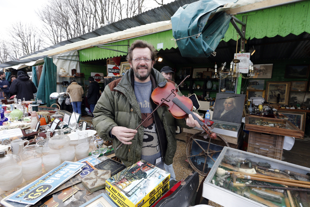 A man holds a violin on March 17, 2013 at the National Antiques and Ham Fair in the western Paris suburb of Chatou.