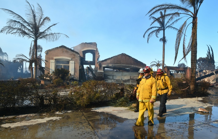 Firemen survey the damage to homes at the Anaheim Hills neighborhood in Anaheim on Oct. 9, 2017, after a fire spread quickly through the area prompting mandatory evacuations and freeway closures.