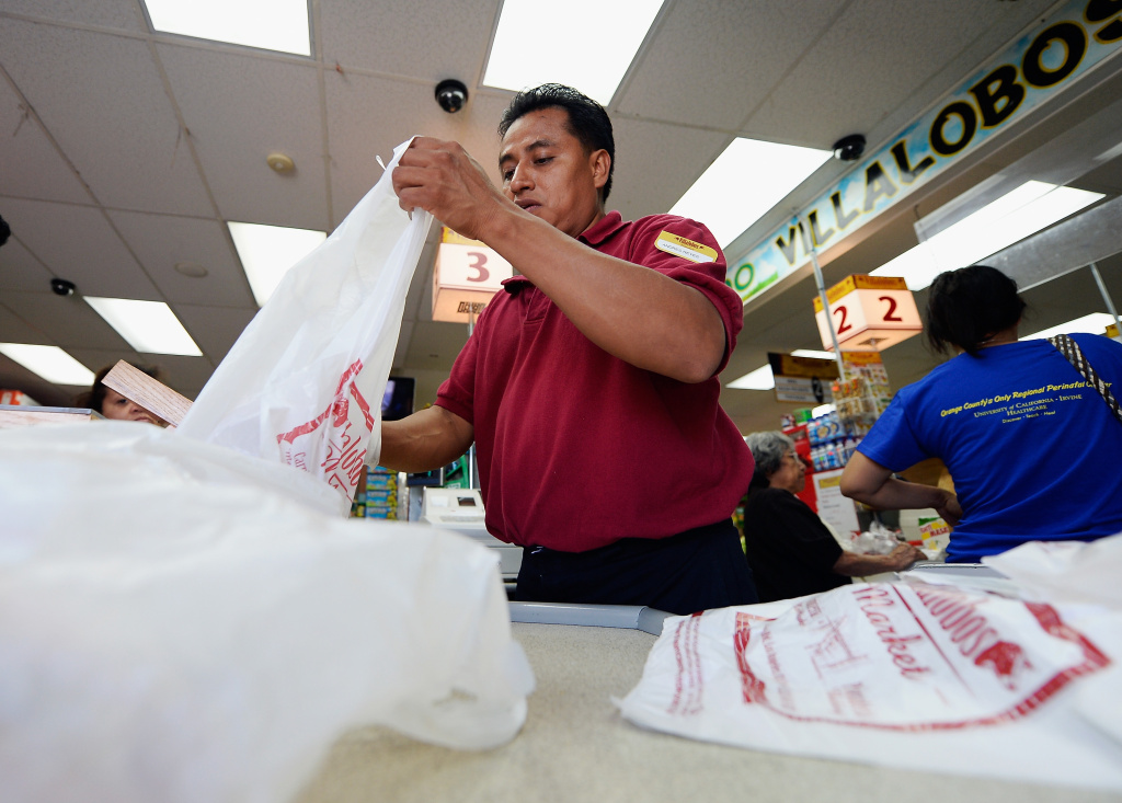 A clerk bags groceries in plastic grocery bags on June 18, 2013.