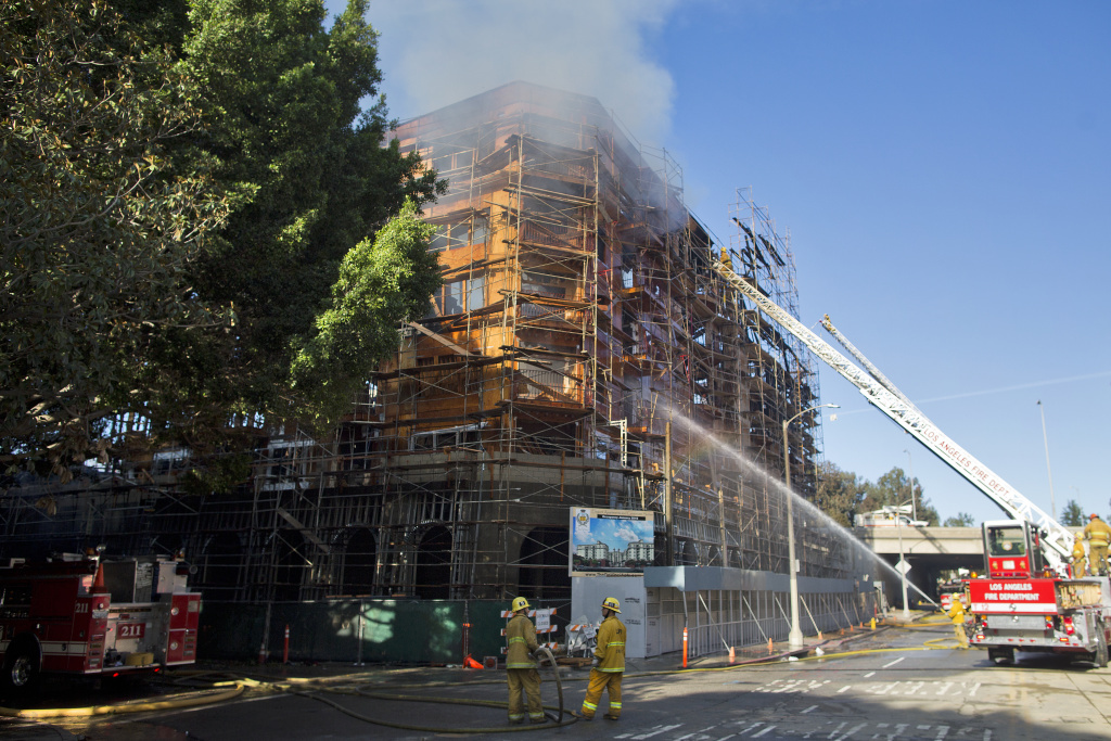 Firefighters spray down smoldering scaffolding after an early-morning fire consumed a seven-story apartment complex that was still under construction in downtown Los Angeles on Monday, Dec. 8, 2014.