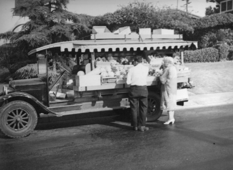 A man, probably the vendor, assists a woman standing in front of a truck parked in a residential neighborhood of Los Angeles, circa 1937.