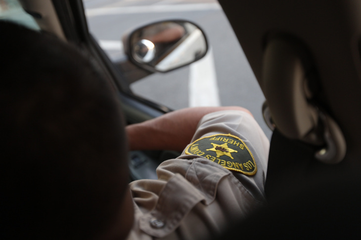 A Los Angeles County Sheriff's deputy sits in a patrol car in a file photo from 2016