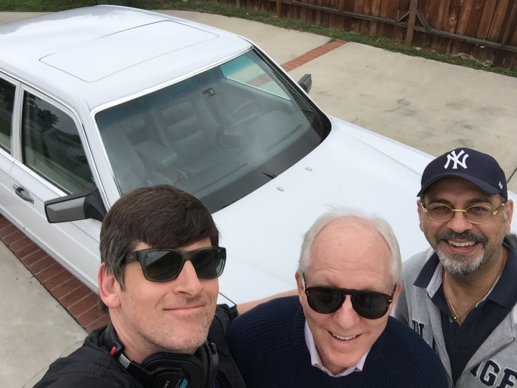 KPCC's John Rabe, sportswriter John Schulian, and Yankees fan and car owner John Evans posing with Joe DiMaggio's 1991 Mercedes in Woodland Hills.