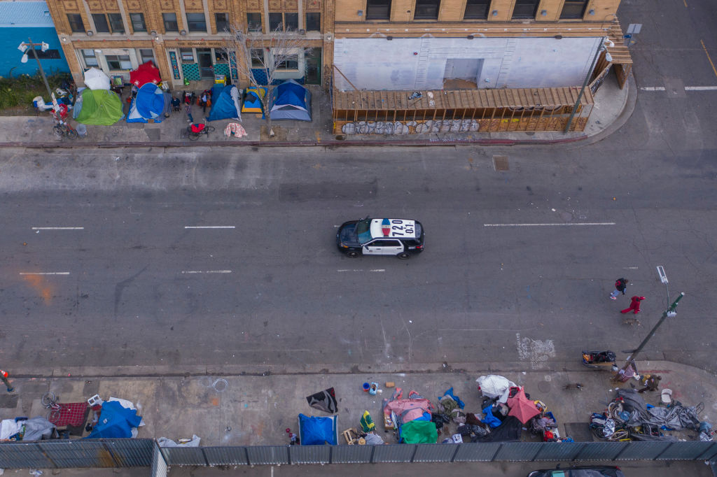 A police car passes homeless people on Skid Row after the new restrictions went into effect as the coronavirus pandemic spreads on March 20, 2020 in Los Angeles, California.