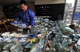The owner of a ceramic shop checks his damaged wares following the massive 8.9-magnitude earthquake in Tokyo on March 11, 2011. The huge earthquake shook Japan, unleashing a powerful tsunami that sent ships crashing into the shore and carried cars through the streets of coastal towns.
