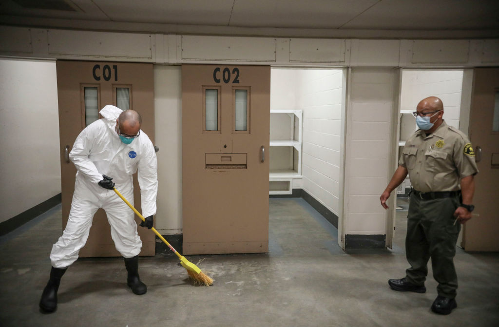 A Sheriff's deputy overlooks a Inmate sweeping at the San Diego County Jail on April 24, 2020 in San Diego, California.