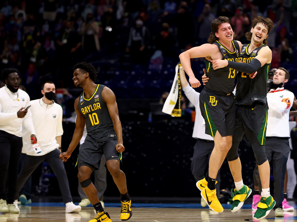 Baylor players Adam Flagler #10, Matthew Mayer #24 and Jackson Moffatt #13 celebrate after defeating the Gonzaga Bulldogs in the National Championship game of the 2021 NCAA Men's Basketball Tournament at Lucas Oil Stadium.